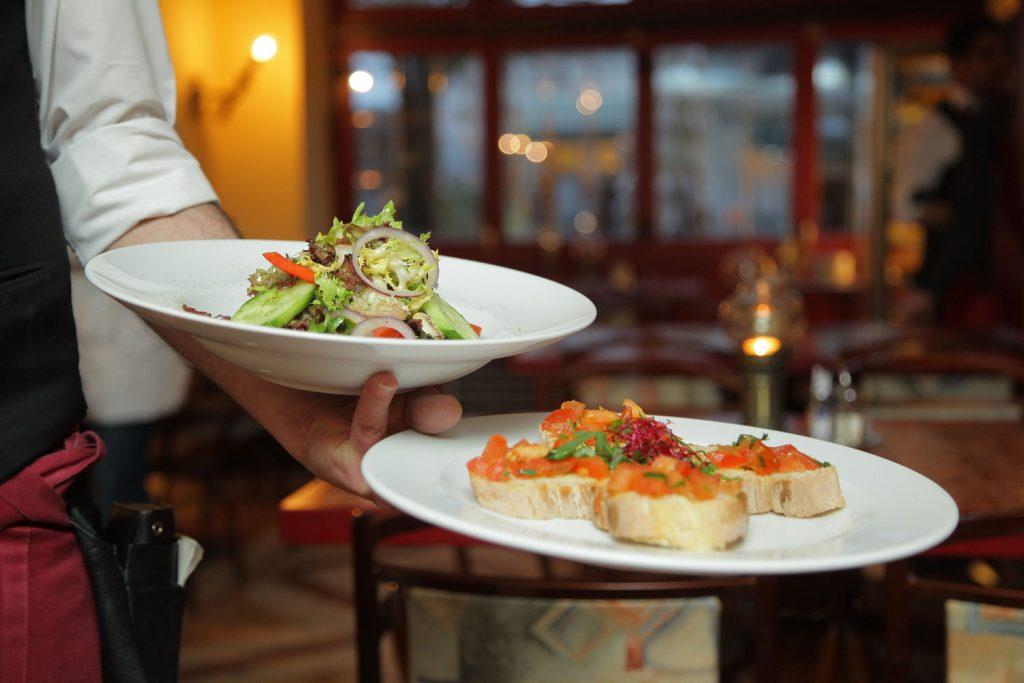 camarero llevando dos platos en una mano