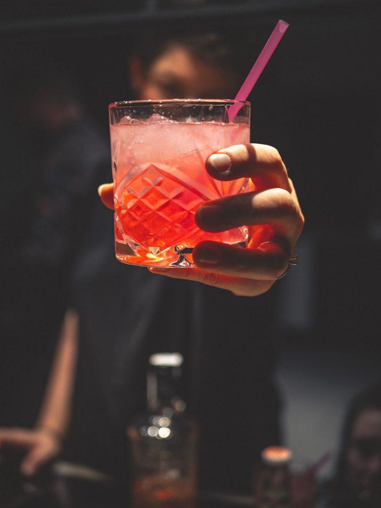 barman sirviendo un cóctel naranja