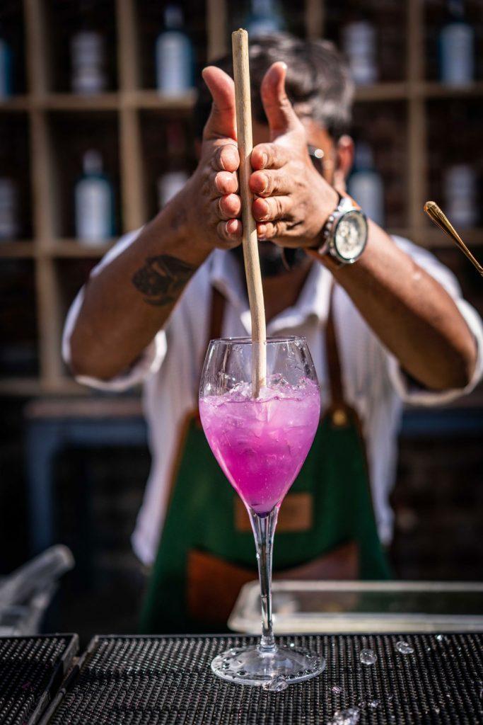 mixólogo preparando un cóctel rosa